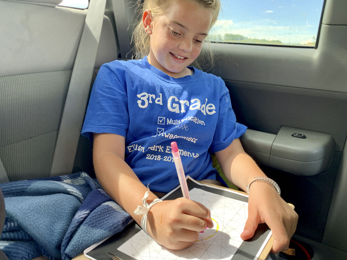 Girl in car coloring while on a road trip